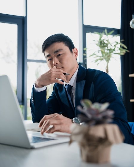 Asian man taking a test on his computer